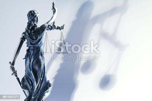 A rear view of the statue of lady justice with her shadow projected on the wall behind her