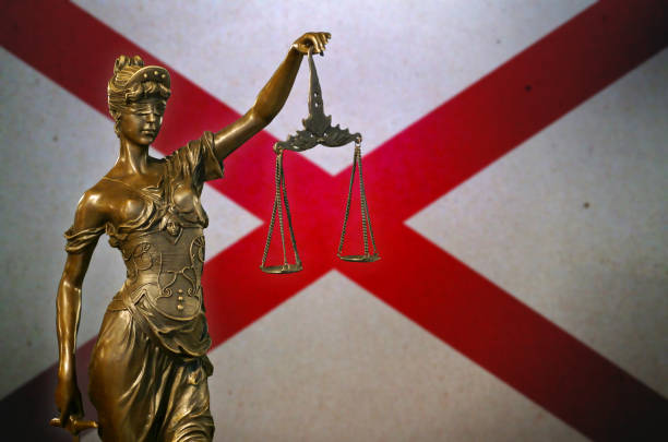 Lady Justice before a flag of Alabama stock photo
