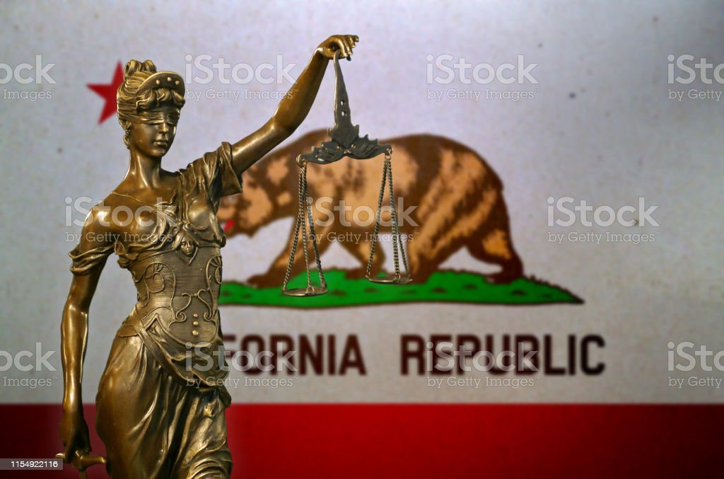 Lady Justice before a flag of California Close-up of a small bronze statuette of Lady Justice before a flag of California. American Culture Stock Photo