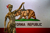 Close-up of a small bronze statuette of Lady Justice before a flag of California.