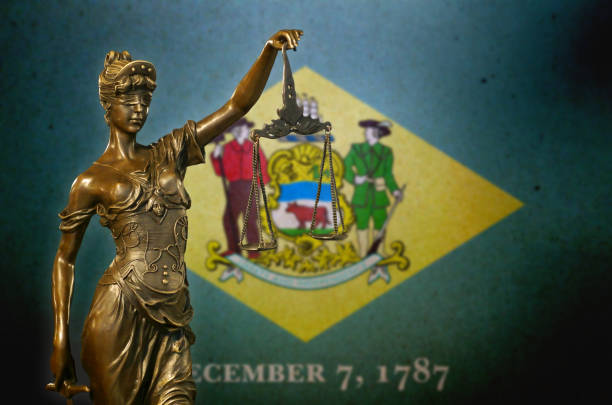 Lady Justice before a flag of Delaware stock photo