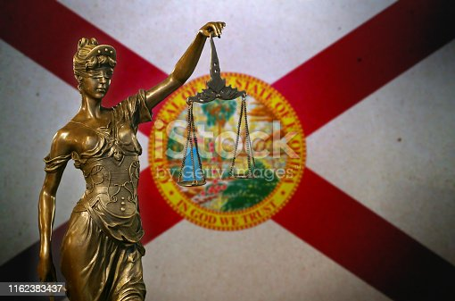 Close-up of a small bronze statuette of Lady Justice before a flag of Florida.