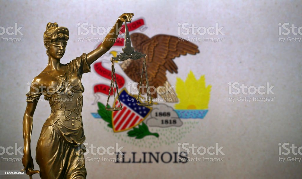 Lady Justice before a flag of Illinois Close-up of a small bronze statuette of Lady Justice before a flag of Illinois. American Culture Stock Photo