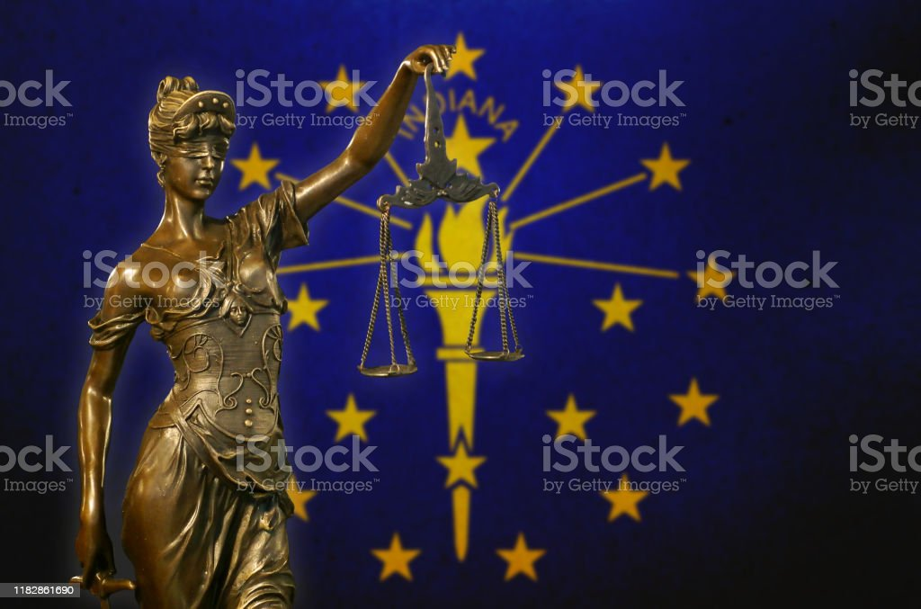 Lady Justice before a flag of Indiana Close-up of a small bronze statuette of Lady Justice before a flag of Indiana. American Culture Stock Photo