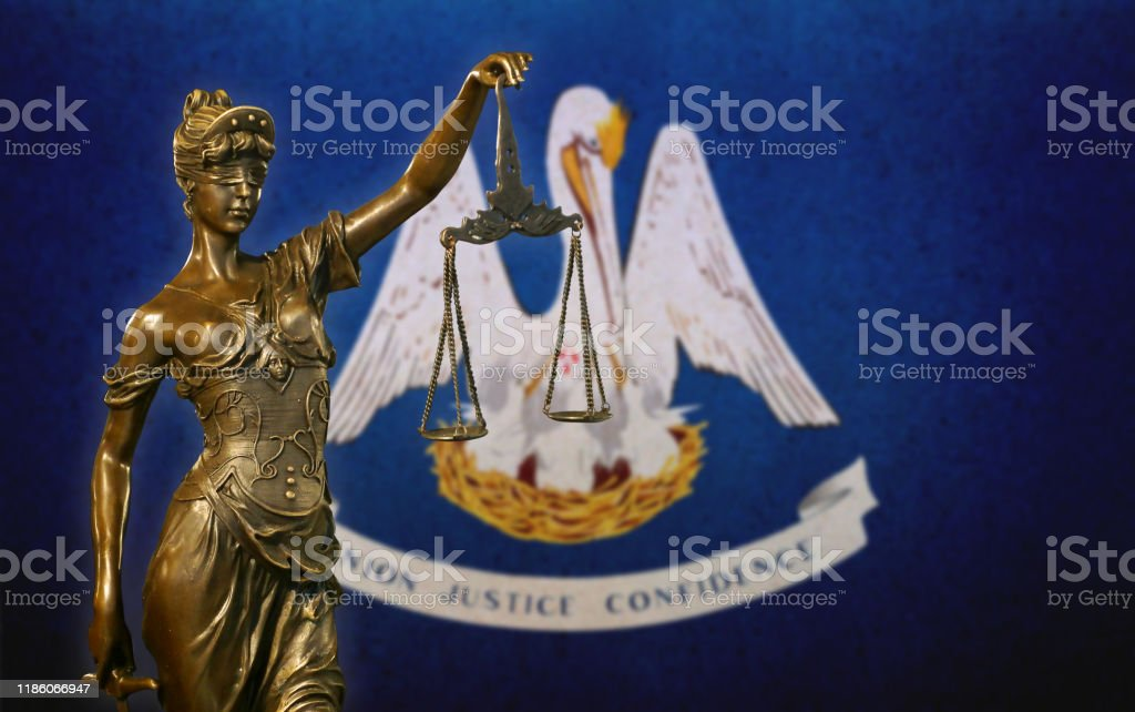 Lady Justice before a flag of Louisiana Close-up of a small bronze statuette of Lady Justice before a flag of Louisiana. American Culture Stock Photo
