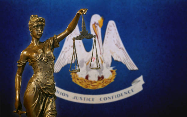 Lady Justice before a flag of Louisiana stock photo