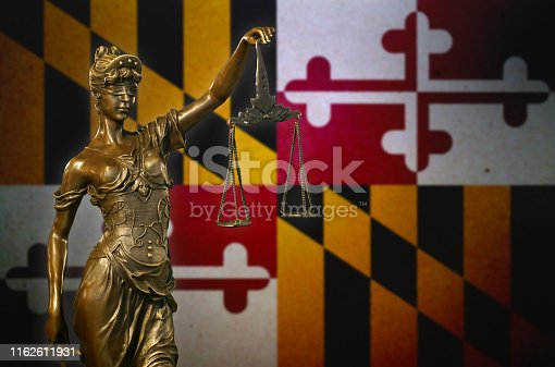 Close-up of a small bronze statuette of Lady Justice before a flag of Maryland.