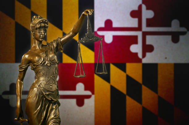 Lady Justice before a flag of Maryland stock photo
