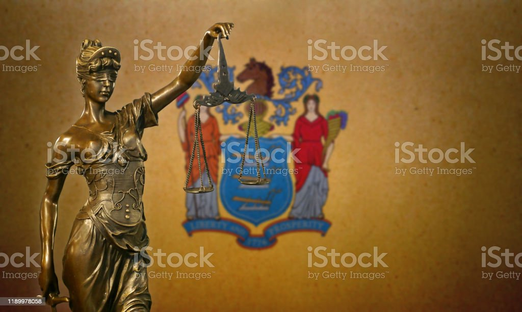 Lady Justice before a flag of New Jersey Close-up of a small bronze statuette of Lady Justice before a flag of New Jersey. American Culture Stock Photo