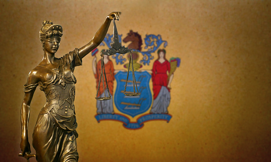 Lady Justice Before A Flag Of New Jersey Stock Photo - Download Image Now