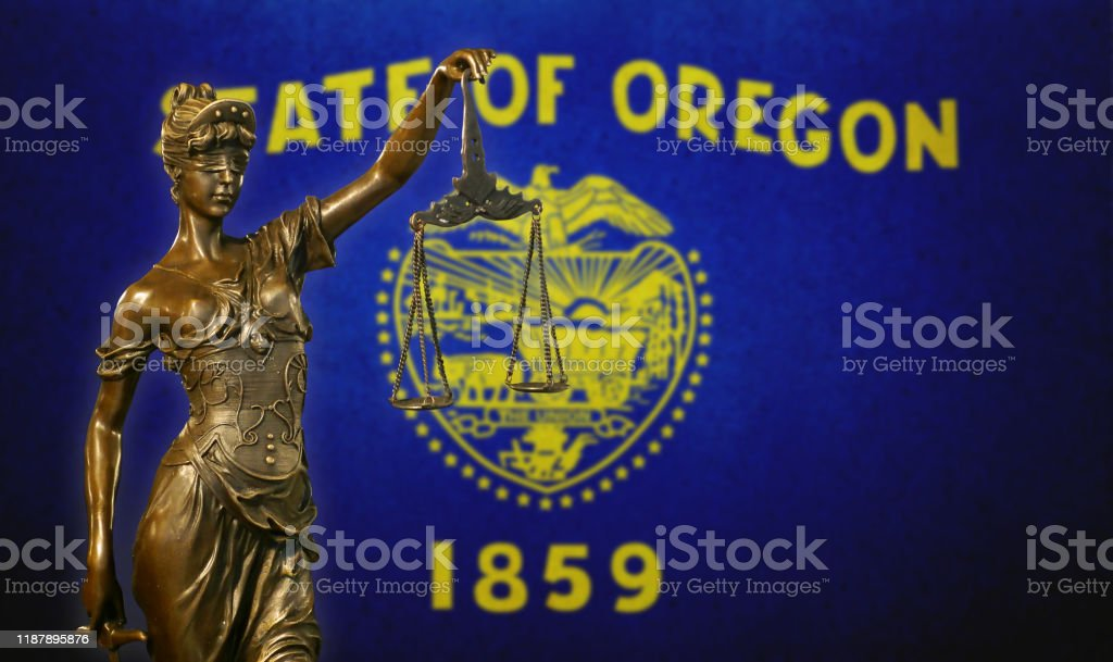 Lady Justice before a flag of Oregon Close-up of a small bronze statuette of Lady Justice before a flag of Oregon. American Culture Stock Photo