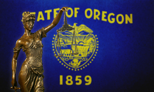 Lady Justice Before A Flag Of Oregon Stock Photo - Download Image Now