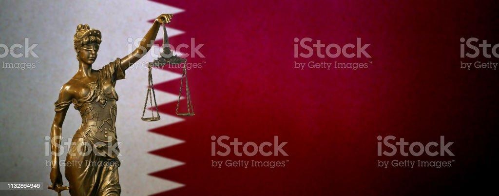 Lady Justice ante una bandera de Qatar - foto de stock