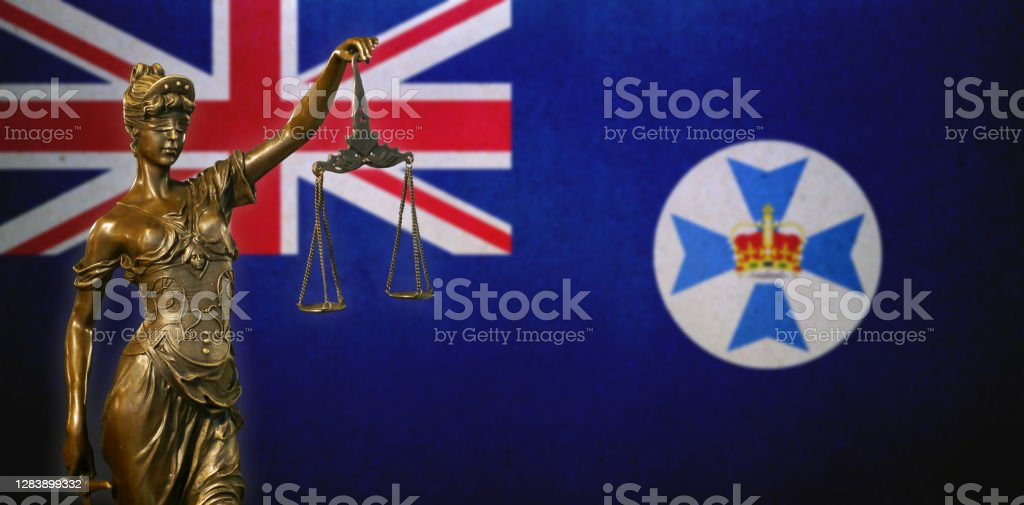 Lady Justice before a flag of Queensland Close-up of a small bronze statuette of Lady Justice before a flag of Queensland (Australia). Australia Stock Photo