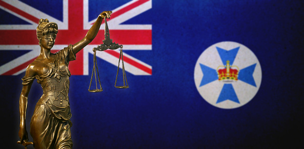 Lady Justice Before A Flag Of Queensland Stock Photo - Download Image Now
