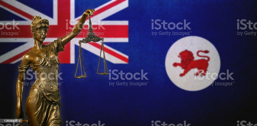 Lady Justice before a flag of Tasmania Close-up of a small bronze statuette of Lady Justice before a flag of Tasmania (Australia). Australia Stock Photo