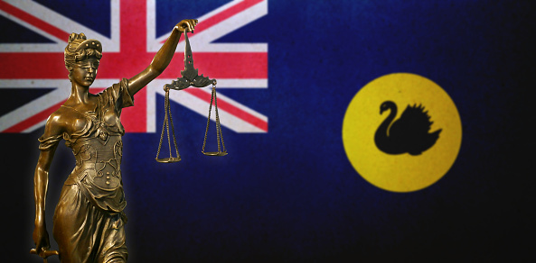 Lady Justice Before A Flag Of Western Australia Stock Photo - Download Image Now