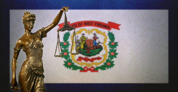 Lady Justice before a West Virginia state flag Close-up of a small bronze statuette of Lady Justice before a flag of West Virginia. west virginia us state stock pictures, royalty-free photos & images