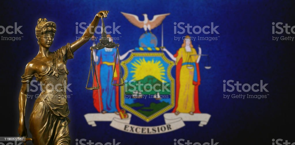 Lady Justice before the New York State Flag Close-up of a small bronze statuette of Lady Justice before a flag of New York. American Culture Stock Photo
