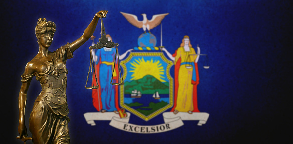 Lady Justice Before The New York State Flag Stock Photo - Download Image Now