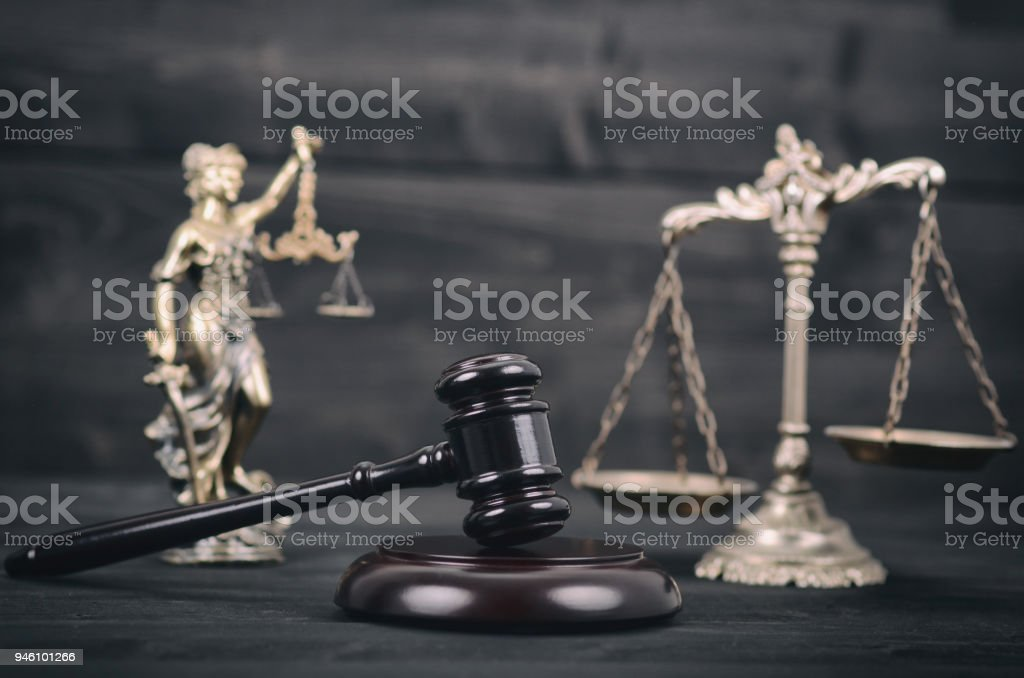 Lady Justice, Scales of Justice and Judge Gavel on a black wooden background. stock photo