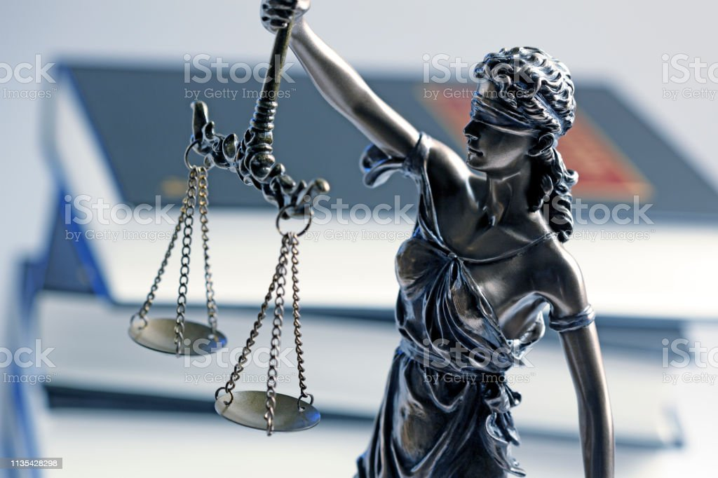 Lady Justice Statue And Gavel In Front Of Sack Of Law Books stock photo