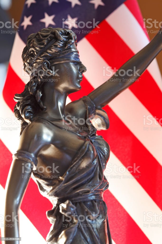 Lady Justice Statue In Front Of American Flag stock photo