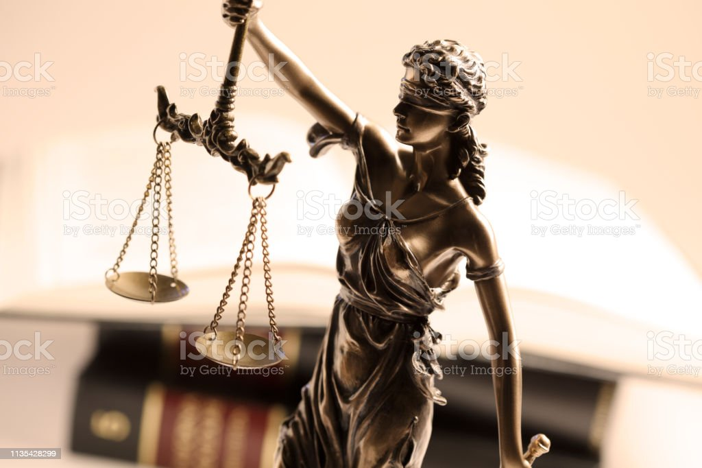 Lady Justice Statue In Front Of Open Law Book stock photo