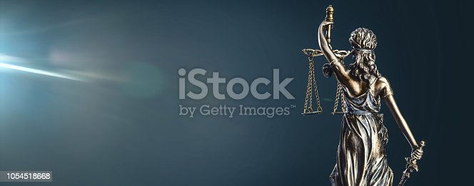 Statue of lady justice on dark background - rear view with copy space.