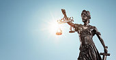 istock Lady justice, Themis sculpture over clear blue sky 1319214916