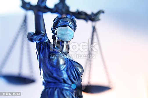 A close up of the the lady justice photographed from a very low camera angle wearing a protective face mask.