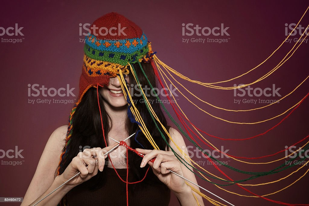 Lady knitting on her own hat royalty free stockfoto