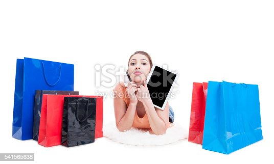 istock Lady laying around shopping bags and holding card and tablet 541565638