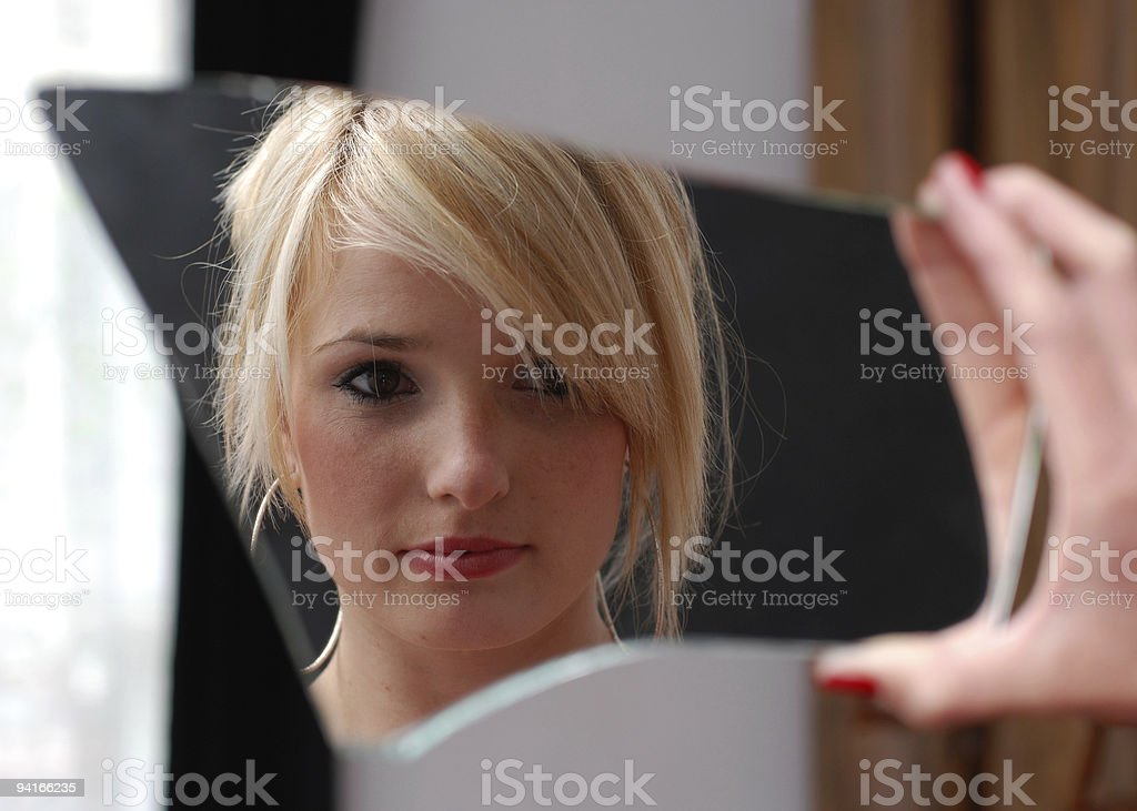 Lady looking at herself in mirror stock photo