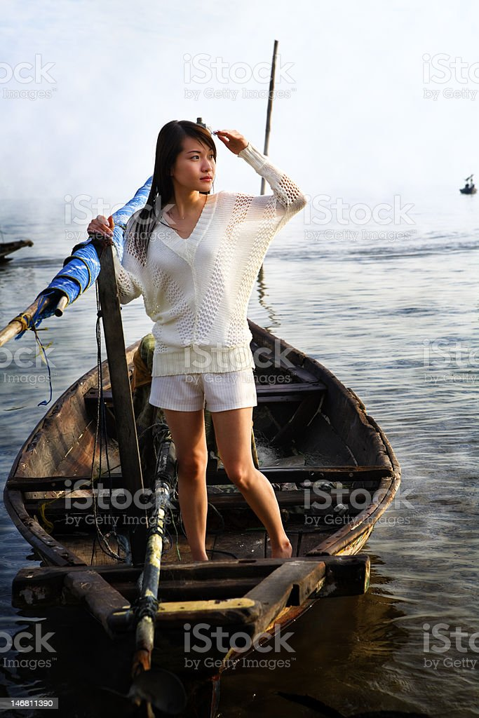 Lady looking at sunrise on traditional boat royalty-free stock photo