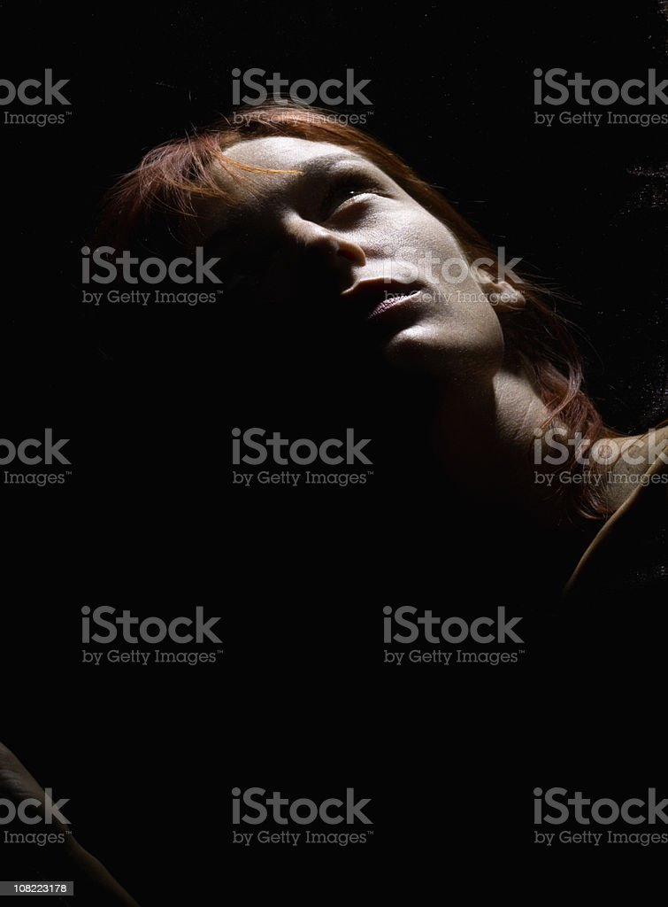 lady looking up into the sunlight in the dark stock photo