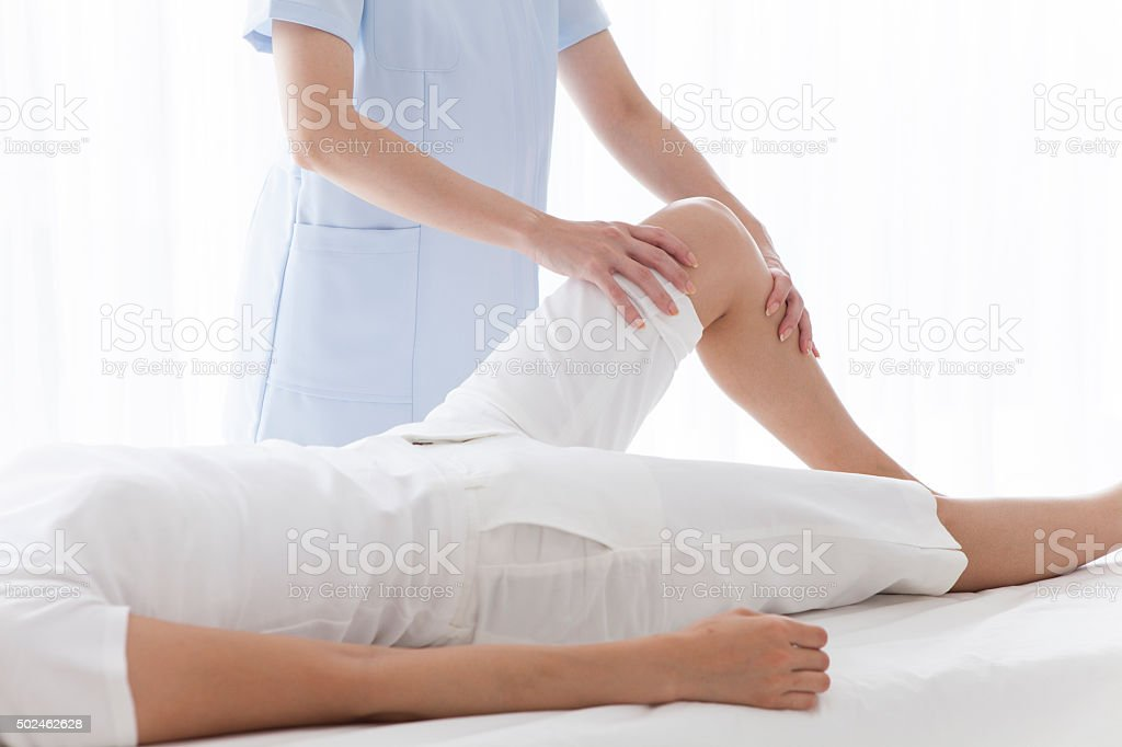 Lady masseur giving female patient a foot reflexology. stock photo