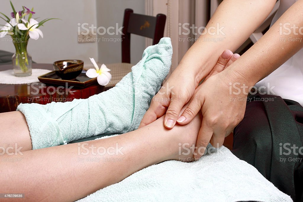 Lady masseur giving patient a leg massage royalty-free stock photo