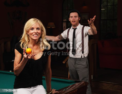 This pretty lady is holding her guy's pool ball hostage - teasing him by flipping it up and down - keeping it out of his reach.