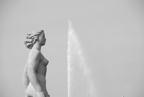 Picture of a statue of beautiful lady taken along Quai Gustave Ador, Lake Geneva, Switzerland. In the background is the Geneva Jet D'Eau.