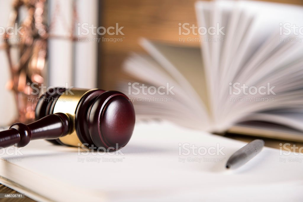 Lady of justice, gavel and books on wooden table stock photo