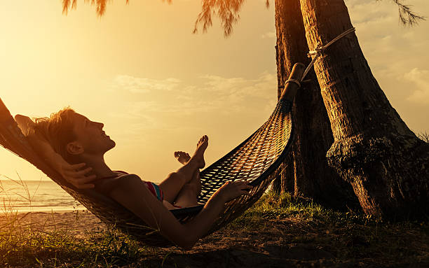 Lady on the beach Lady relaxing in the hammock on the beach netting stock pictures, royalty-free photos & images