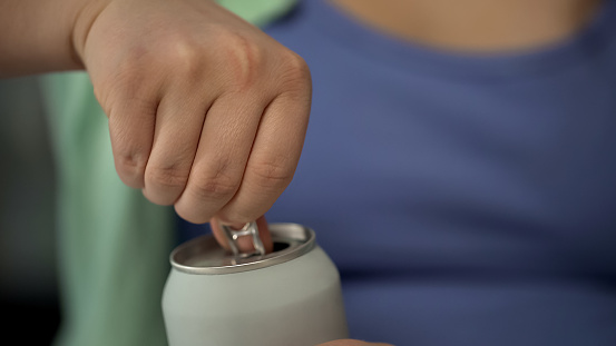 lady opening can to drink soda beverage containing much