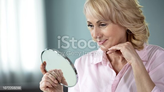 661896674istockphoto Lady over 50 looking at herself in mirror, rejoicing at result of skin lifting 1072203200