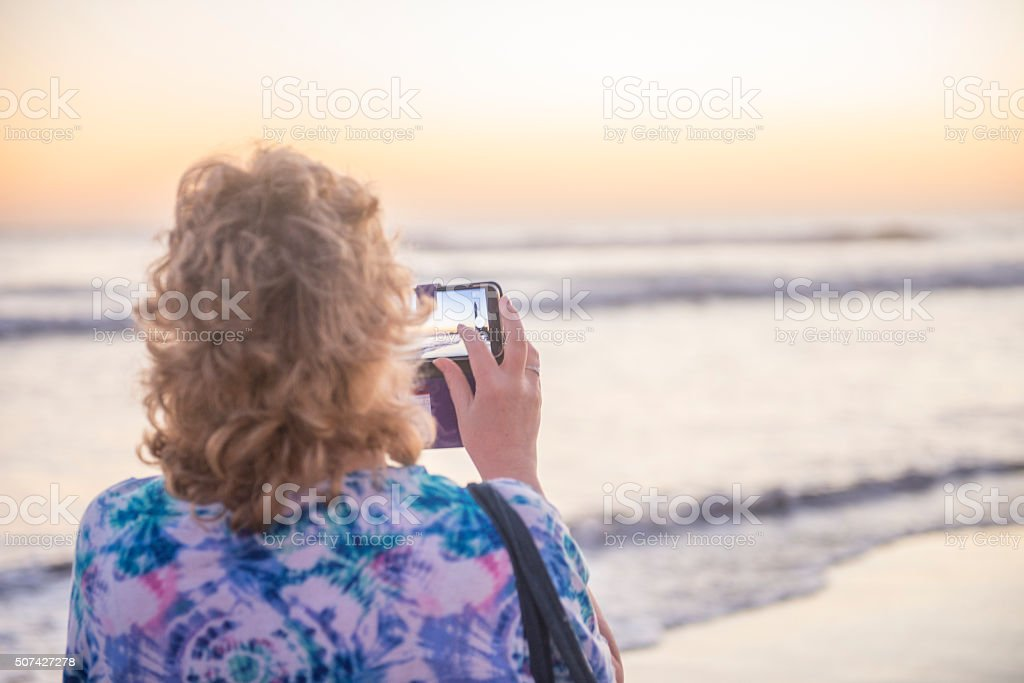 Lady photographing the sunset royalty-free stock photo