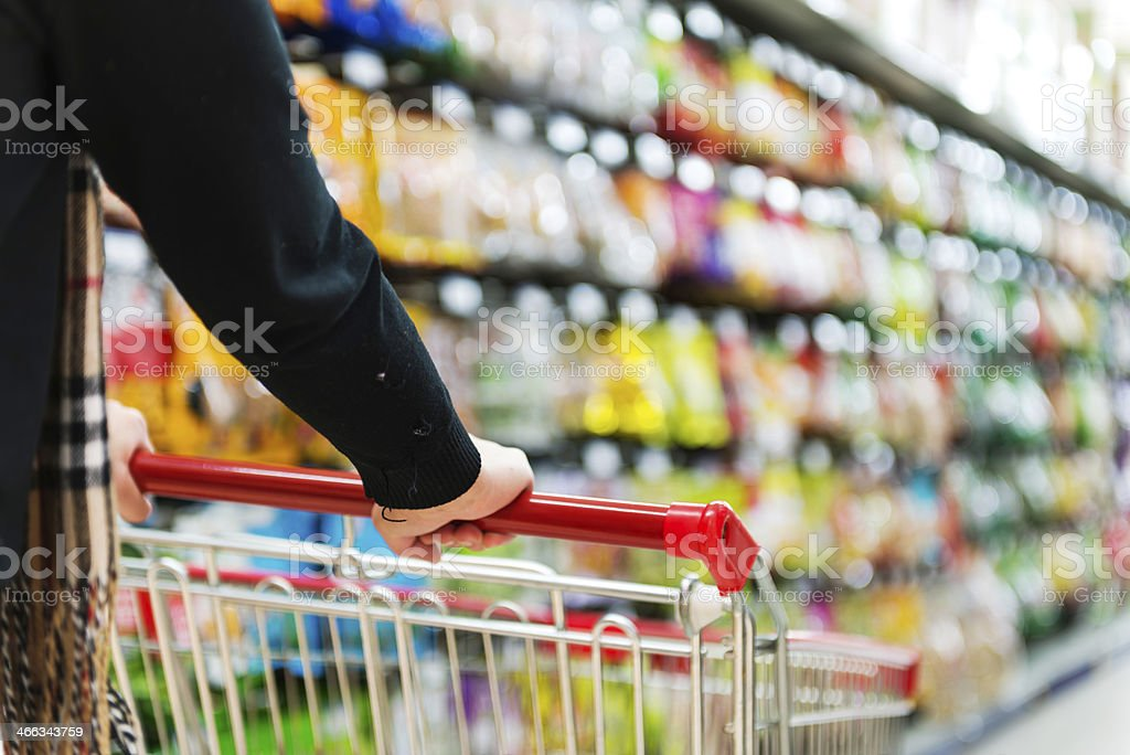 Lady pushing a shopping cart in the supermarket. stock photo