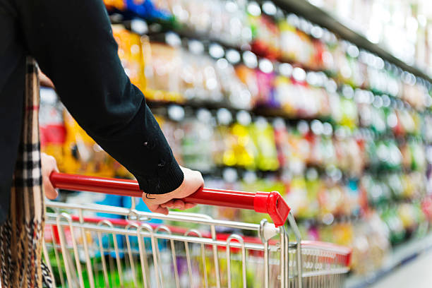 lady pushing a shopping cart in the supermarket. - consumer products stock photos and pictures