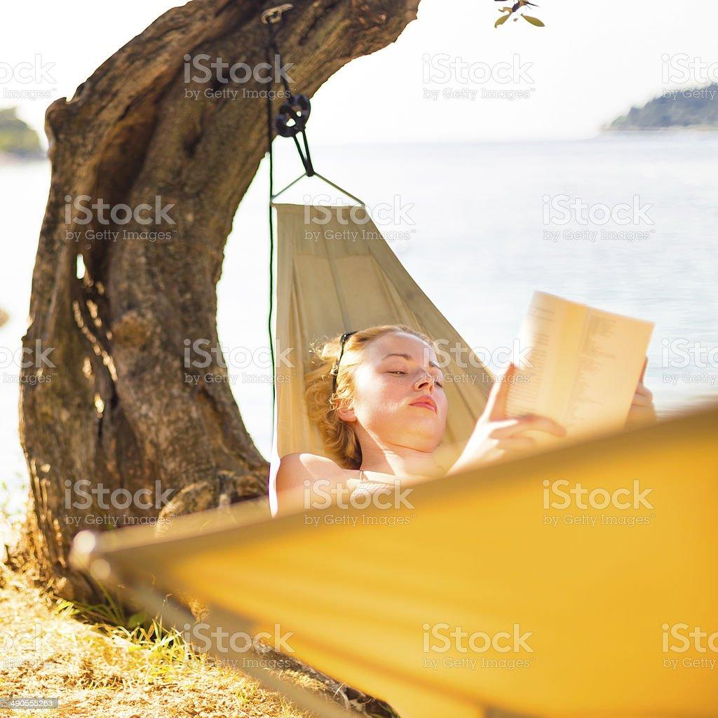 Frau liest ein Buch in der Hängematte. Lizenzfreies stock-foto