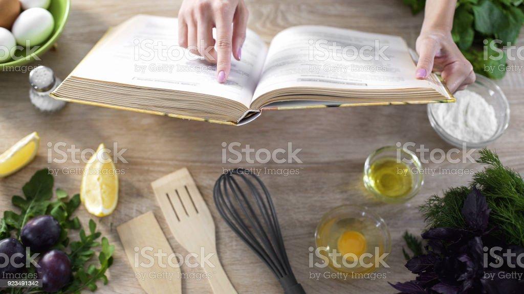 Lady lesen Pizza Rezept in kulinarischen Buch zu Hause mit Geschirr auf Tisch – Foto