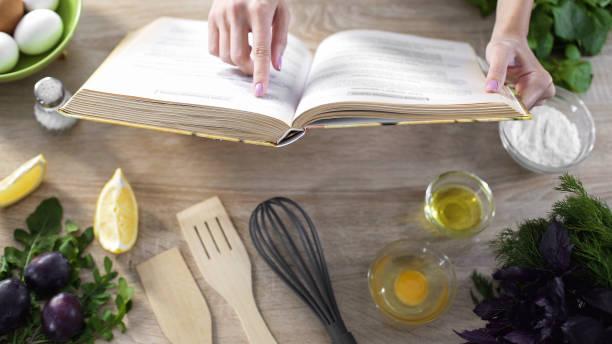 senhora pizza receita no livro de culinária em casa com utensílios de cozinha na mesa de leitura - receita - fotografias e filmes do acervo